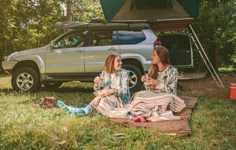 Women friends resting under blanket in campsite