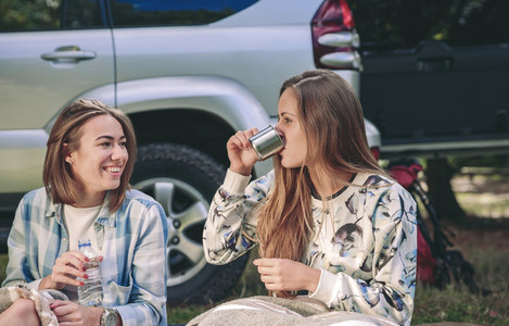 Woman drinking cup of coffee with friend in campsite