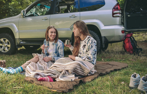Women friends talking and resting under blanket