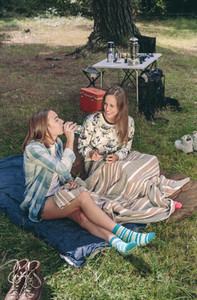 Woman drinking water with friend in campsite