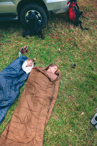 Women resting inside of sleeping bags with 4x4 on background