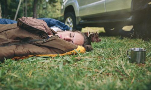 Young woman resting in the nature on sleeping bag