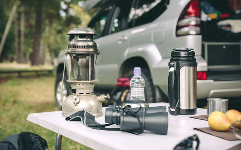 Oil lamp thermos and binoculars over camping table