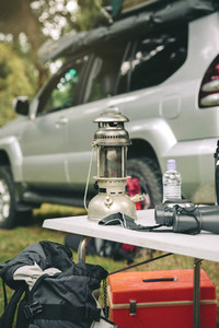 Oil lamp and binoculars over camping table