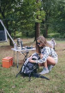 Woman preparing backpack for a hiking trip