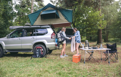 Young women in campsite packing blanket for hiking