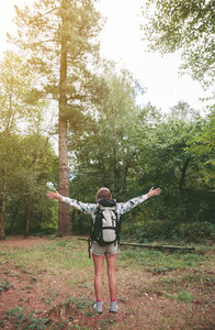 Hiker woman with backpack raising her arms into the forest