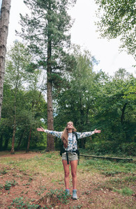 Hiker woman with backpack raising her arms