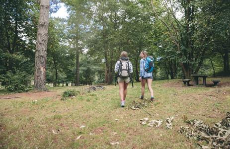 Two women friends with backpacks walking