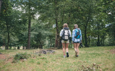 Two women friends with backpacks walking