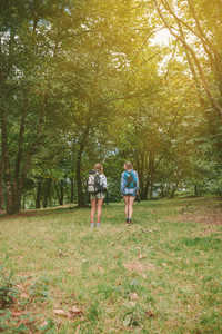 Two women friends with backpacks standing in forest