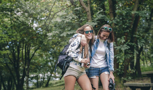 Women friends laughing while walking in forest
