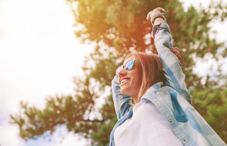 Woman with sunglasses raising her arms over nature background