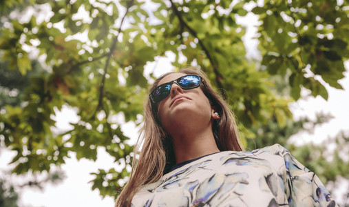 Woman with sunglasses standing over nature background