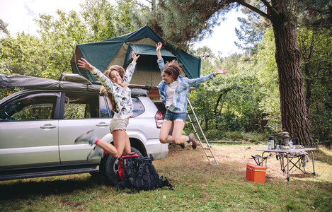 Women friends jumping in campsite into the forest
