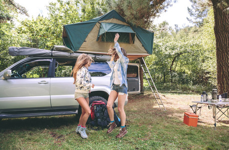 Women friends having fun in campsite into the forest