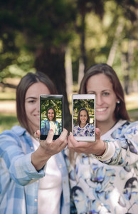 Women showing smartphones with their selfie photos