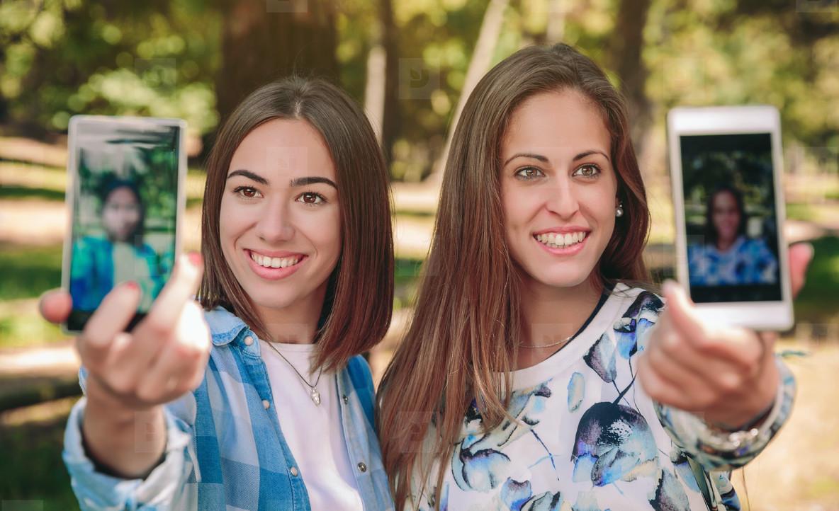 Women taking selfie photos with smartphones in nature