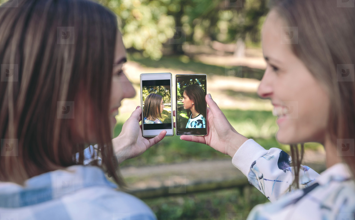 Women showing smartphones with side view portraits photos