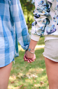 Closeup of women holding hands over nature background