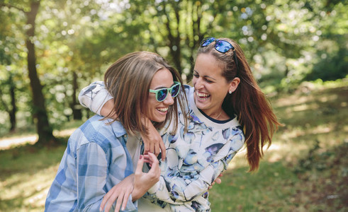 Happy women embracing and laughing over nature background
