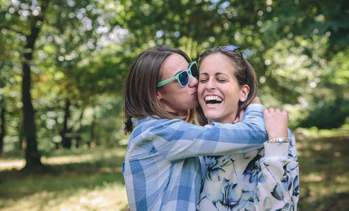 Woman kissing and embracing to female friend laughing