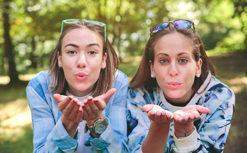Two women friends blowing kiss to camera