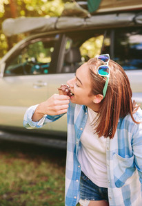 Young woman eating chocolate ice cream in forest