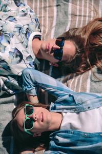 Two women with sunglasses lying taking a sunbath
