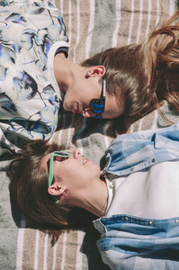 Women friends with sunglasses looking each other lying