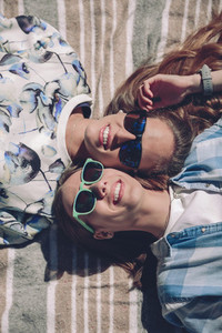 Two women with sunglasses smiling lying in blanket