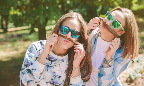 Women having fun doing moustaches with hair
