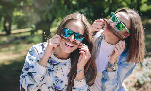 Women doing moustaches with hair and laughing
