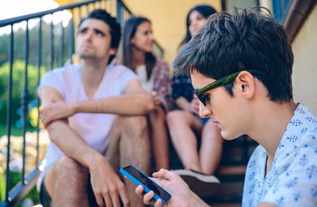 Young man looking a smartphone outdoors with his friends