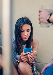 Young woman looking a smartphone outdoors with her friends