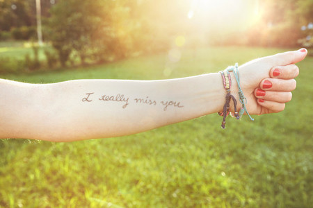 Female arm with text  I really miss you  written in skin