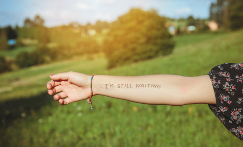 Female arm with text  Im still waiting  written in skin