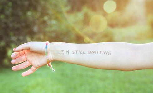 Female arm with text  Im still waiting  written in skin