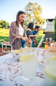 Woman opening beer bottle in summer barbecue