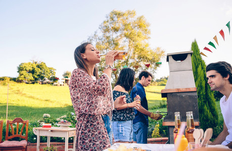 Woman drinking beer in a barbecue with friends