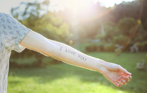 Male arm with text  I love you  written in skin