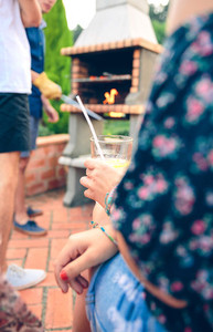 Woman holding lemonade glass and friends cooking in barbecue