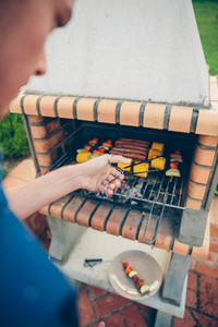 Unrecognizable young man cooking meal in barbecue