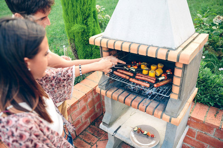 Friends cooking in barbecue on summer party