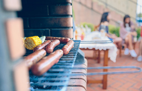 Sausages and corn cobs cooked in a barbecue