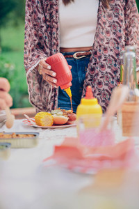 Woman hand pouring ketchup over an american hot dog