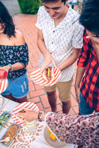 Young man holding hot dog in a barbecue with friends