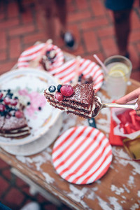Woman with piece of cake in a summer party