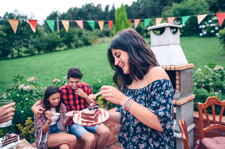 Woman eating piece of cake in summer party