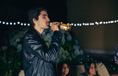 Man drinking bottle of beer in a party